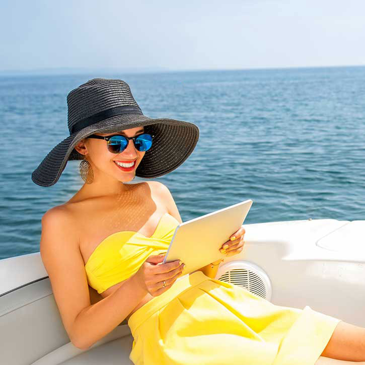 women reading from tablet on superyacht
