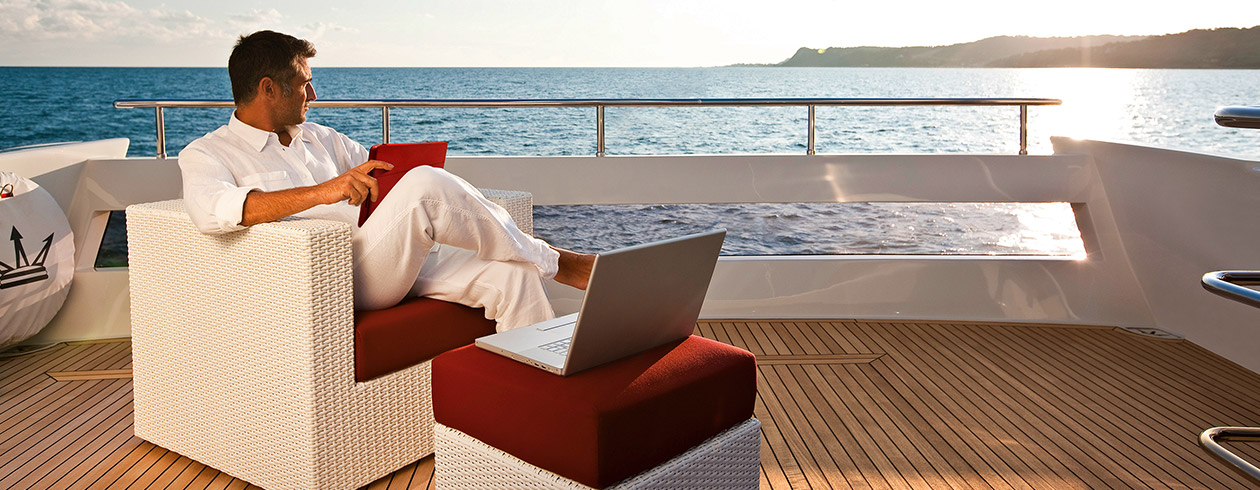 Man on superyacht with laptop